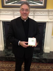 Rev. Robert A. Sirico with a PovertyCure DVD. (Photo by: Lauren Perinovic)